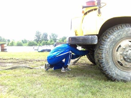Reprezentant Paľo Maťáš sa snaží vydolovať zapadnutý kamión z bahna...