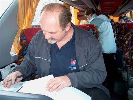 Tréner Ľubomír Hagara sa sústredene venuje nutnej papierovej administratíve na pohodlnom sedadle parádneho autobusu-mercedesu DAK KIABA Nováky.