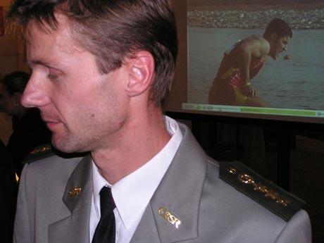Peter Páleš prekvapil, na vyhlásenie prišiel v parádnej uniforme dôstojníka slovenskej armády. Symbolické foto, ocenený Peter odchádza z pódia a na projekcii v pozadí olympijský víťaz v C1 mladý Španiel David Cal.