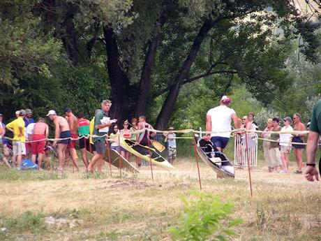 A tak musel Rado už na prvej prenáške doháňať stratu cca 40 metrov. Zatiaľ čo maďari už míňajú a obchádzajú hlúčik okolo odpadnutej Lucie Balákovej (na snímke sedí na zemi vľavo dole vedľa svojej modrej lode), náš pretekár sa ešte len blíži k  rozhodcovi a štartérovi pretekov (ten pán v okuliaroch v zelenom triku s papiermi a minerálkou v rukách), ktorý potom následne odkláňa nechápajúceho Rada doprava. Dodatočne na brehu po pretekoch sa to vysvetlilo, Rado to okomentoval slovami: Vôbec som nevedel, čo chce. Nechápal som prečo ma odkláňa vpravo, veď som bežal správne vo vymedzenom priestore...